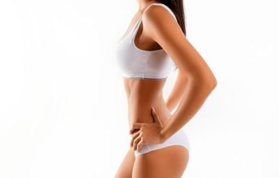 Side view of women with her hands on hips after liposuction body contouring