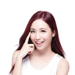 korean beauty smile pointing at her eye after eyelid surgery