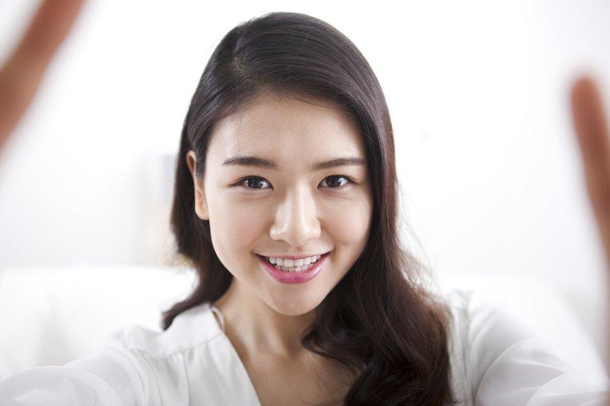 Asian woman looking at camera smiling