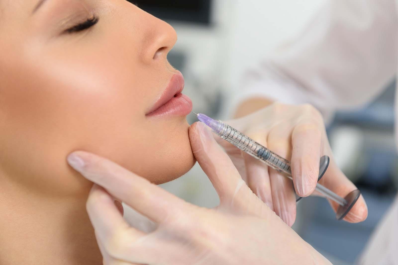 Beautician hand holding syringe of botox near female lips
