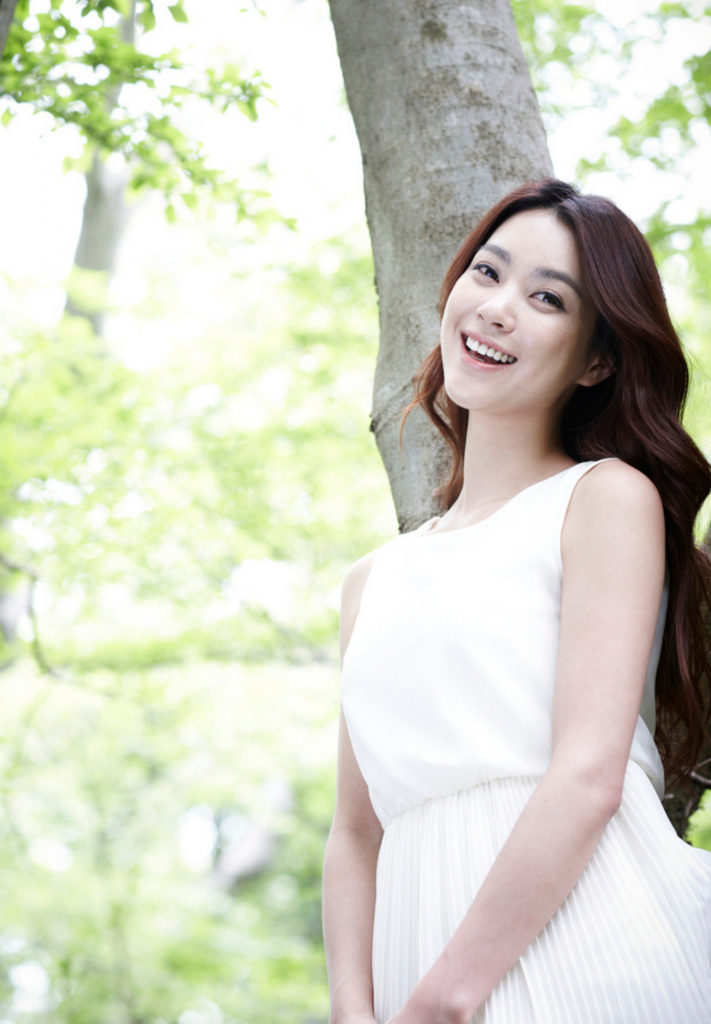 Asian woman standing in white dress smiling with aegyo sal