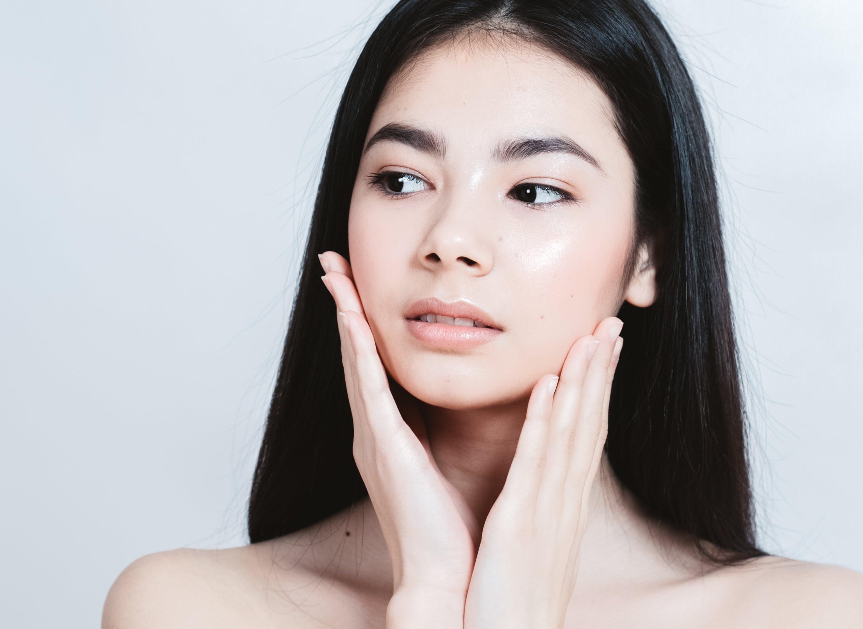 Asian woman touching face for k-beauty